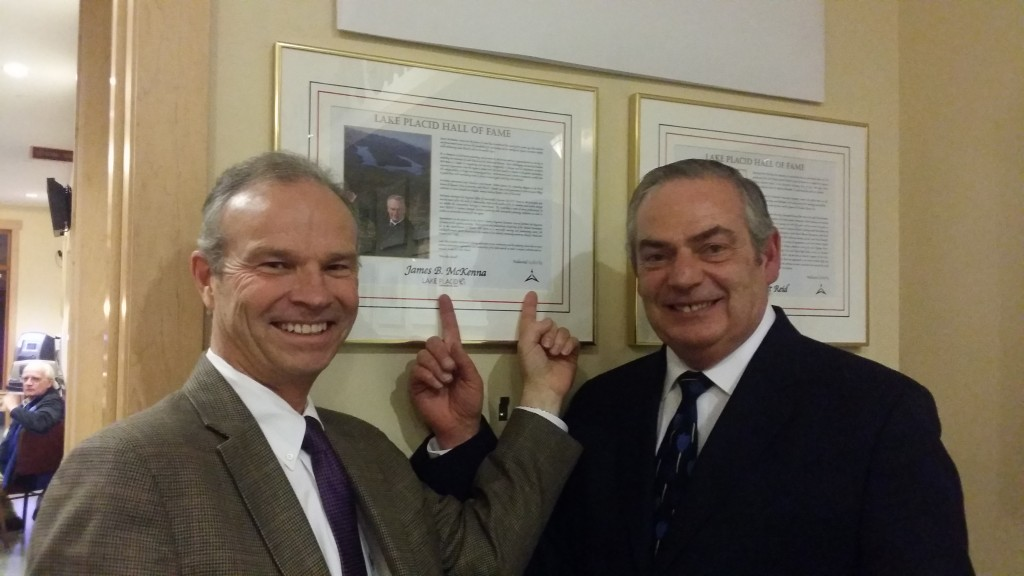 ORDA CEO Ted Blazer and ROOST CEO James McKenna point out their logos on McKenna's Hall of Fame plaque.