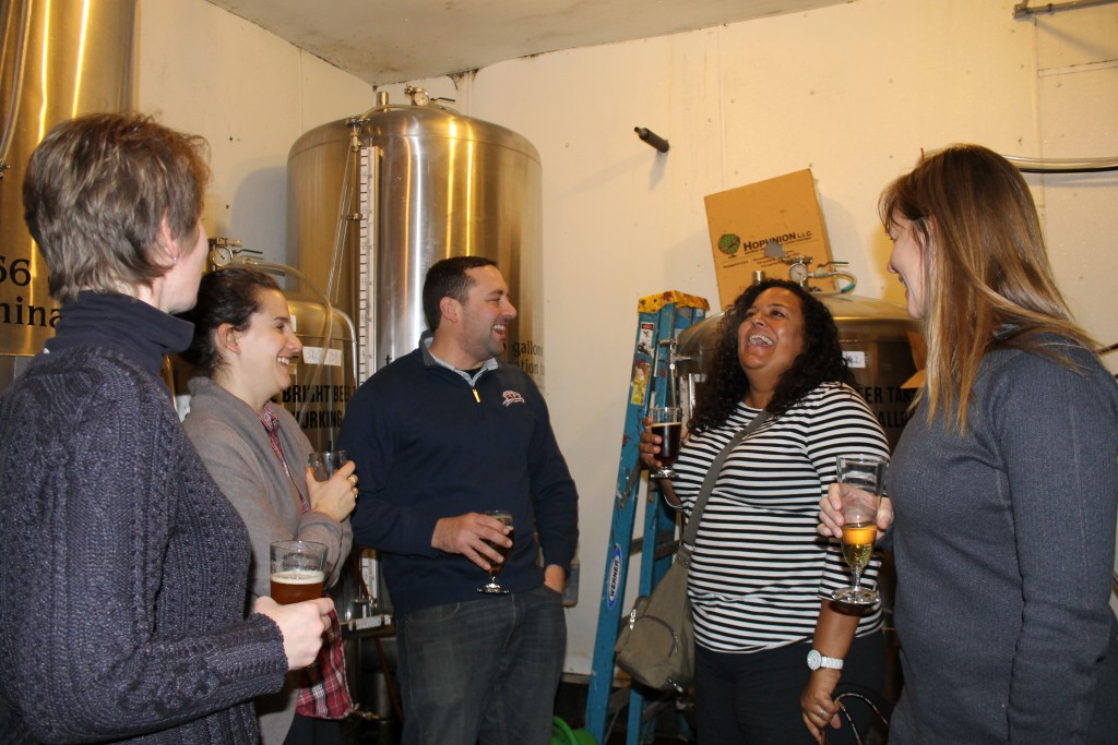 Robby Kane of Great Adirondack Brewing shows the ladies around their apparatus.