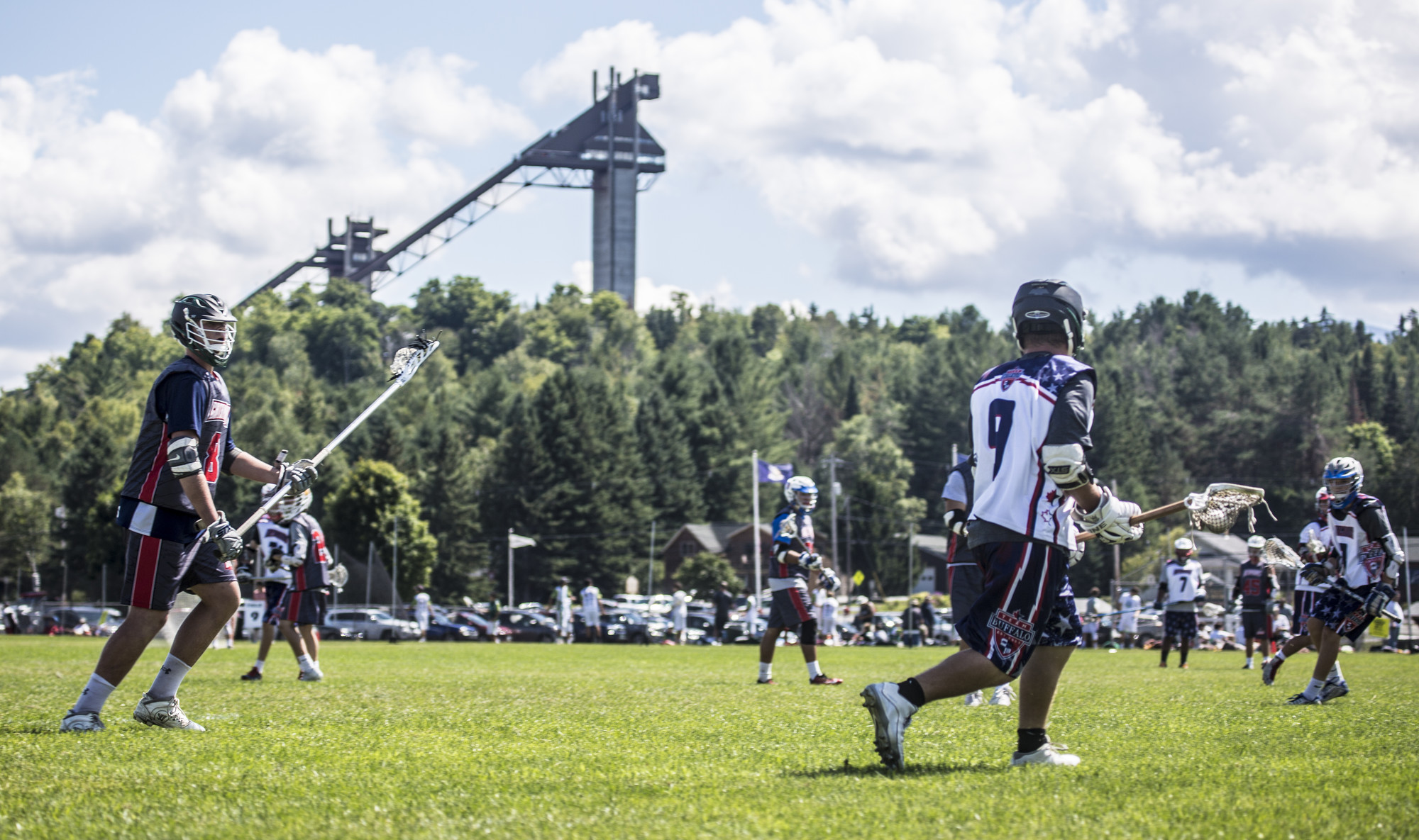 Athletes compete in the Lake Placid Lacrosse Tournament with views of the ski jumps behind them.