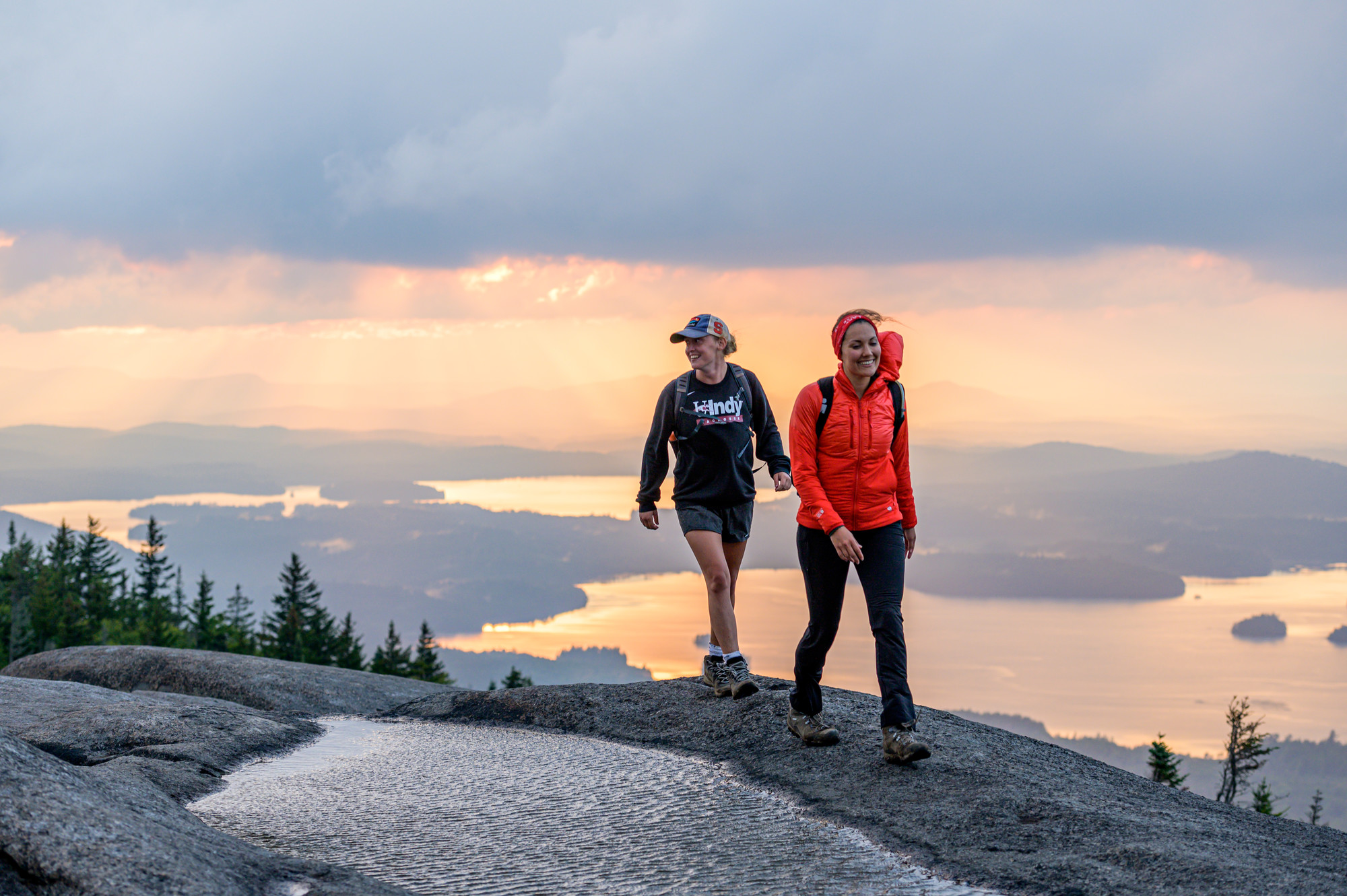 Hikers at the top of Ampersand Mountain with a hazy sunset as the backdrop
