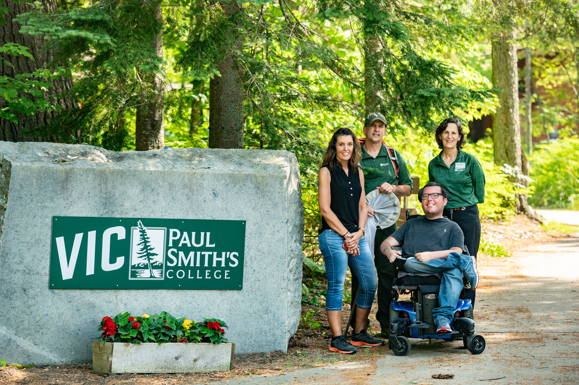 Travel Writer Corey Lee from Curb Free with Cory Lee poses with his mother and two staff members from Paul Smith's College VIC next to the entrance sign on a beautiful summer day..